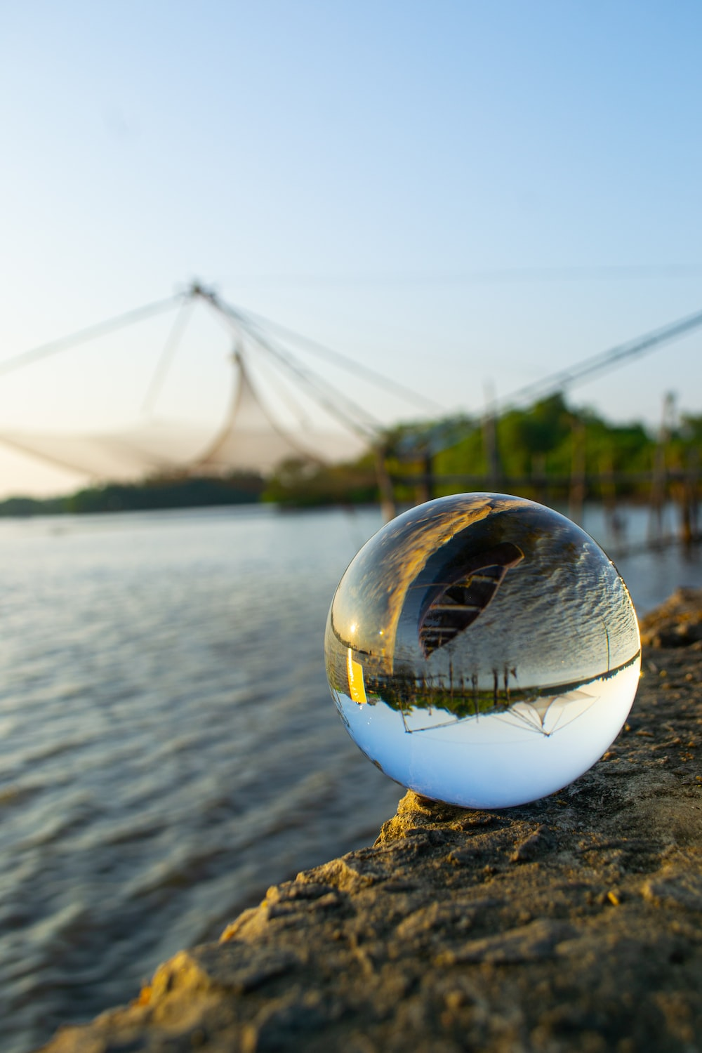 clear glass ball on body of water during daytime