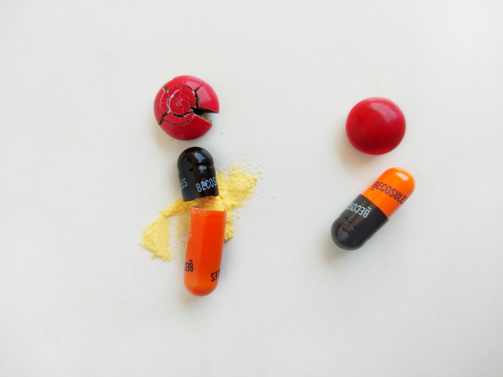 red yellow and black medicine capsules