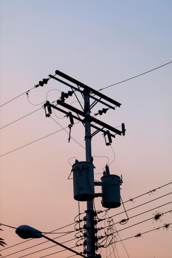 black electricity post under white sky