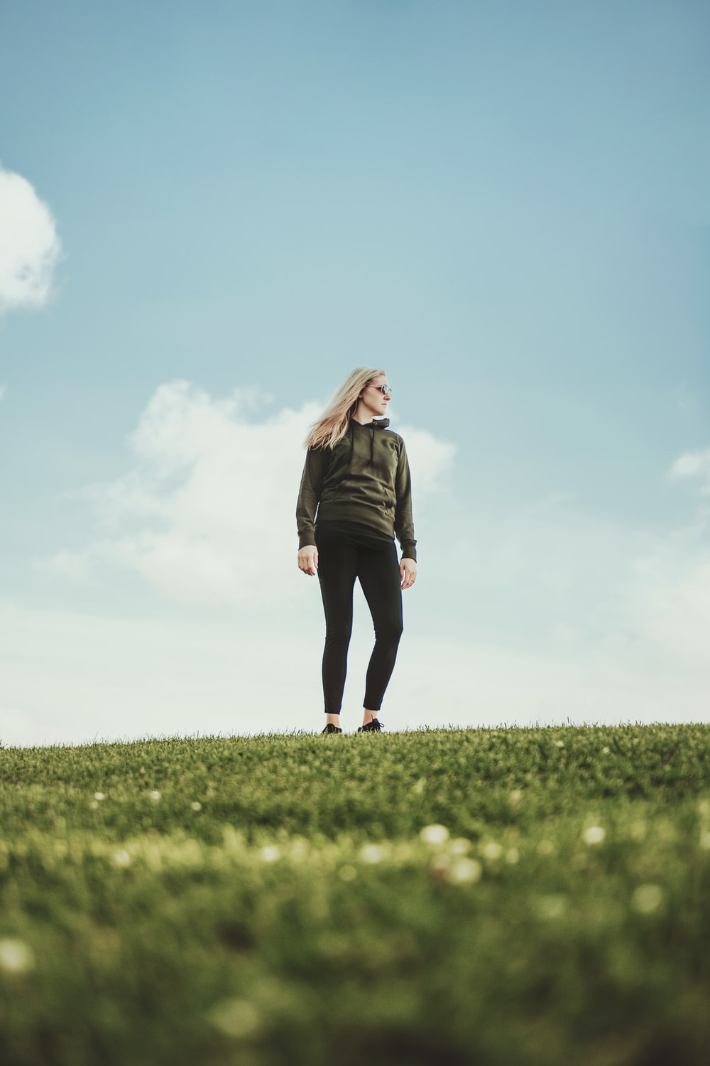 woman in black jacket standing on green grass field under blue sky during daytime