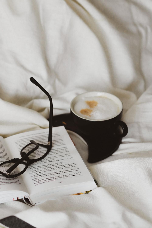 black ceramic mug with coffee on white textile