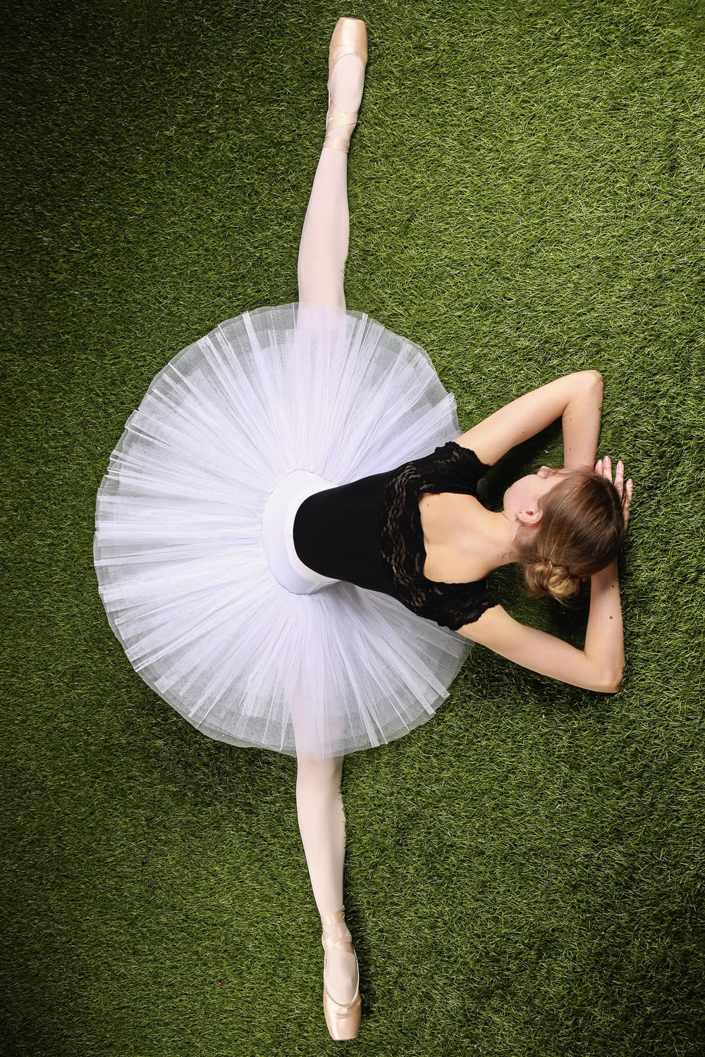 woman in black and white dress lying on green grass field