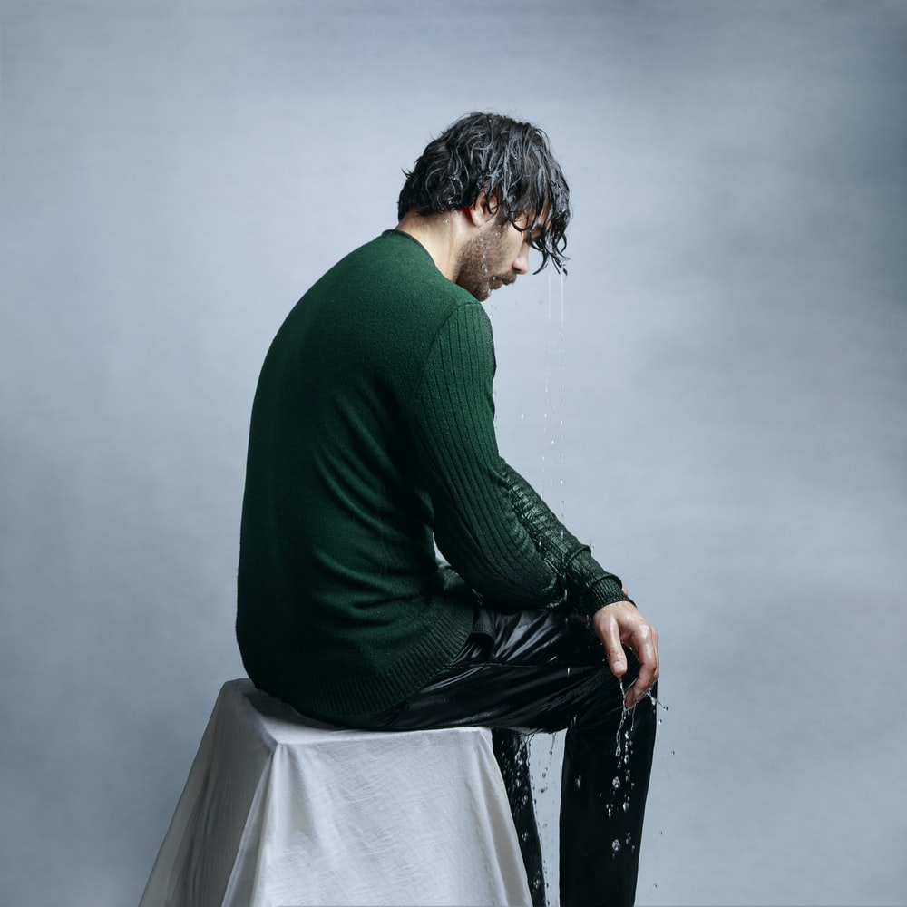 man in green long sleeve shirt and black pants sitting on white chair