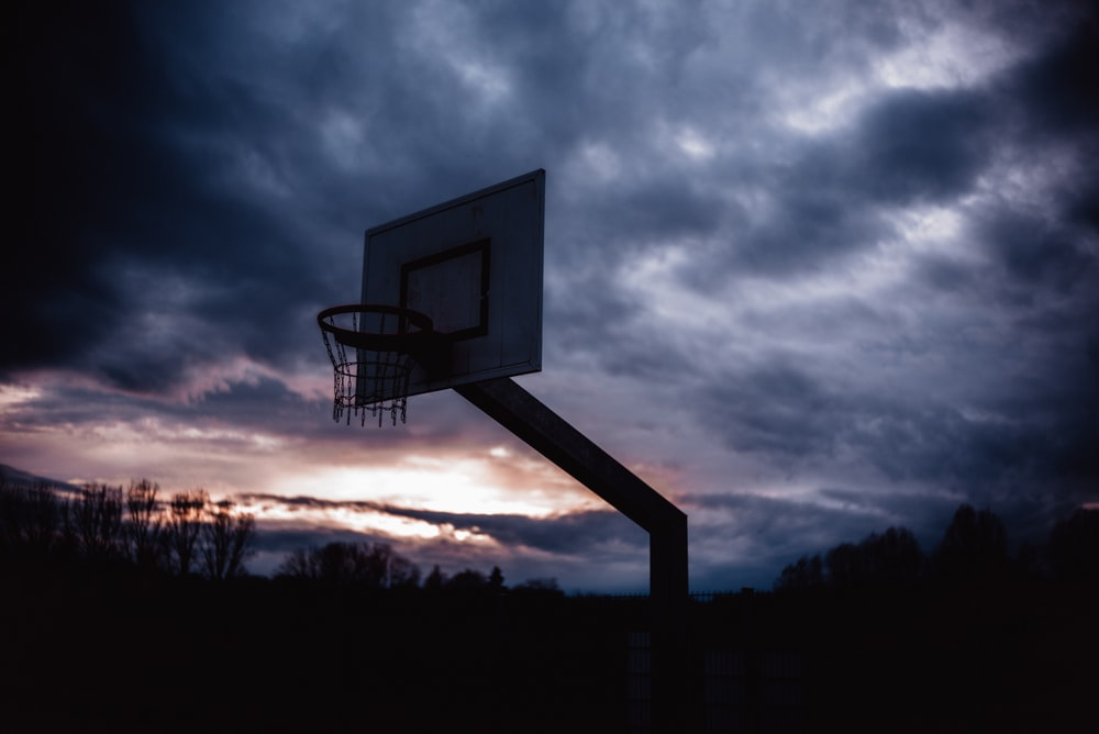 basketball hoop under cloudy sky during daytime