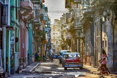 red van on road in between buildings during daytime cuba teams background