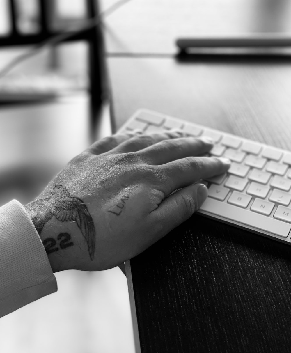 grayscale photo of persons hand on computer keyboard