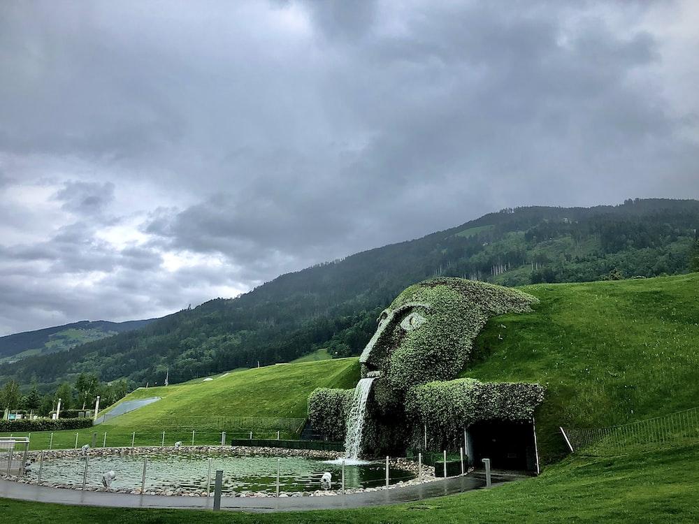 green grass field near green mountain under white clouds during daytime