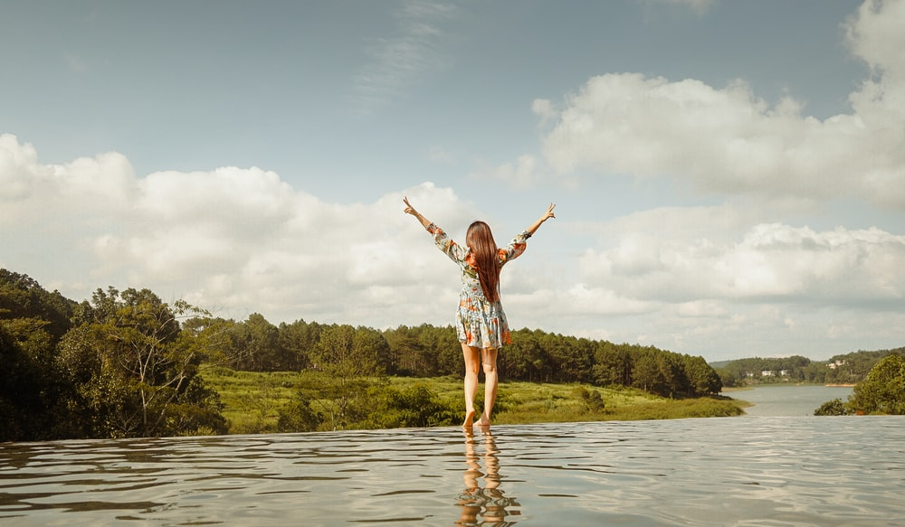 woman in red and white plaid shirt and white shorts standing on water during daytime