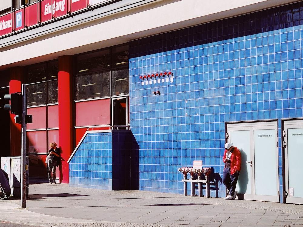 people walking on sidewalk near blue building during daytime