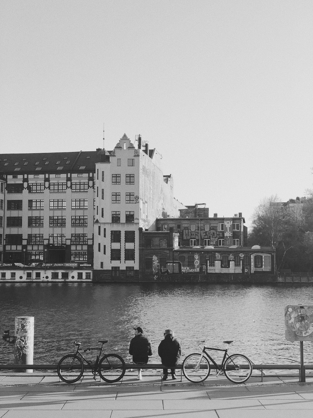 grayscale photo of people walking on sidewalk near body of water and buildings