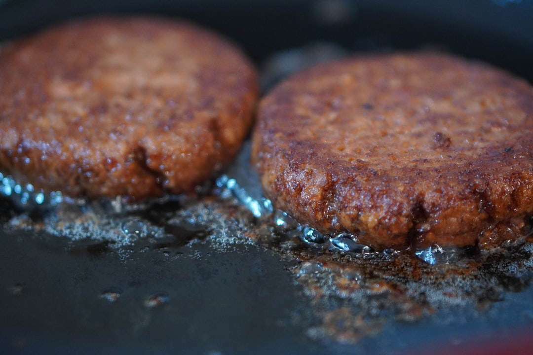 Two vegan burger patties in a black pan, with sizzling vegetable oil.