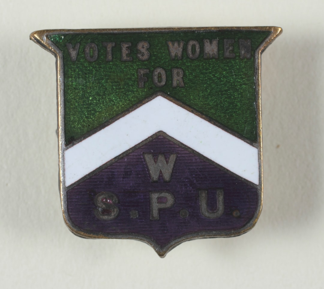 Suffrage Campaigning: Women's Social & Political Union 1906-1914. Badge, [tarnished] metal, enamel, shield-shaped, produced by the Women's Social & Political Union, enamelled purple, green and white background, with metallic inscription: 'Votes for Women ... WSPU'', metal clasp on reverse side. TWL.2004.626.2