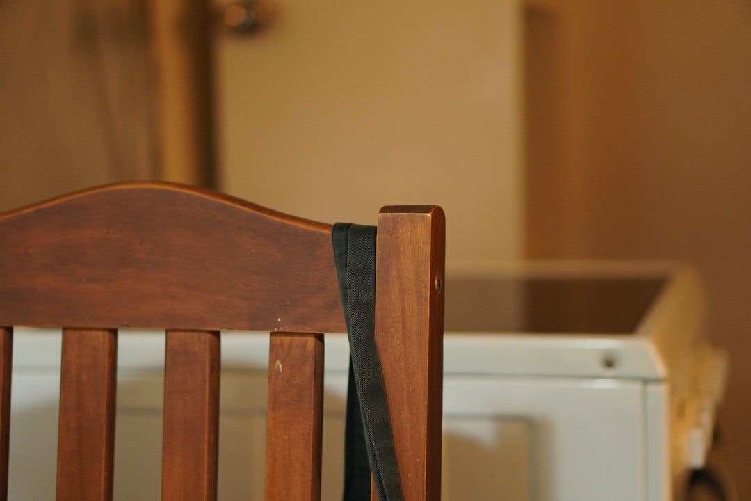 Minimalist view of the backrest of a kitchen chair and stove. A bag is hanging over the chair's back.
