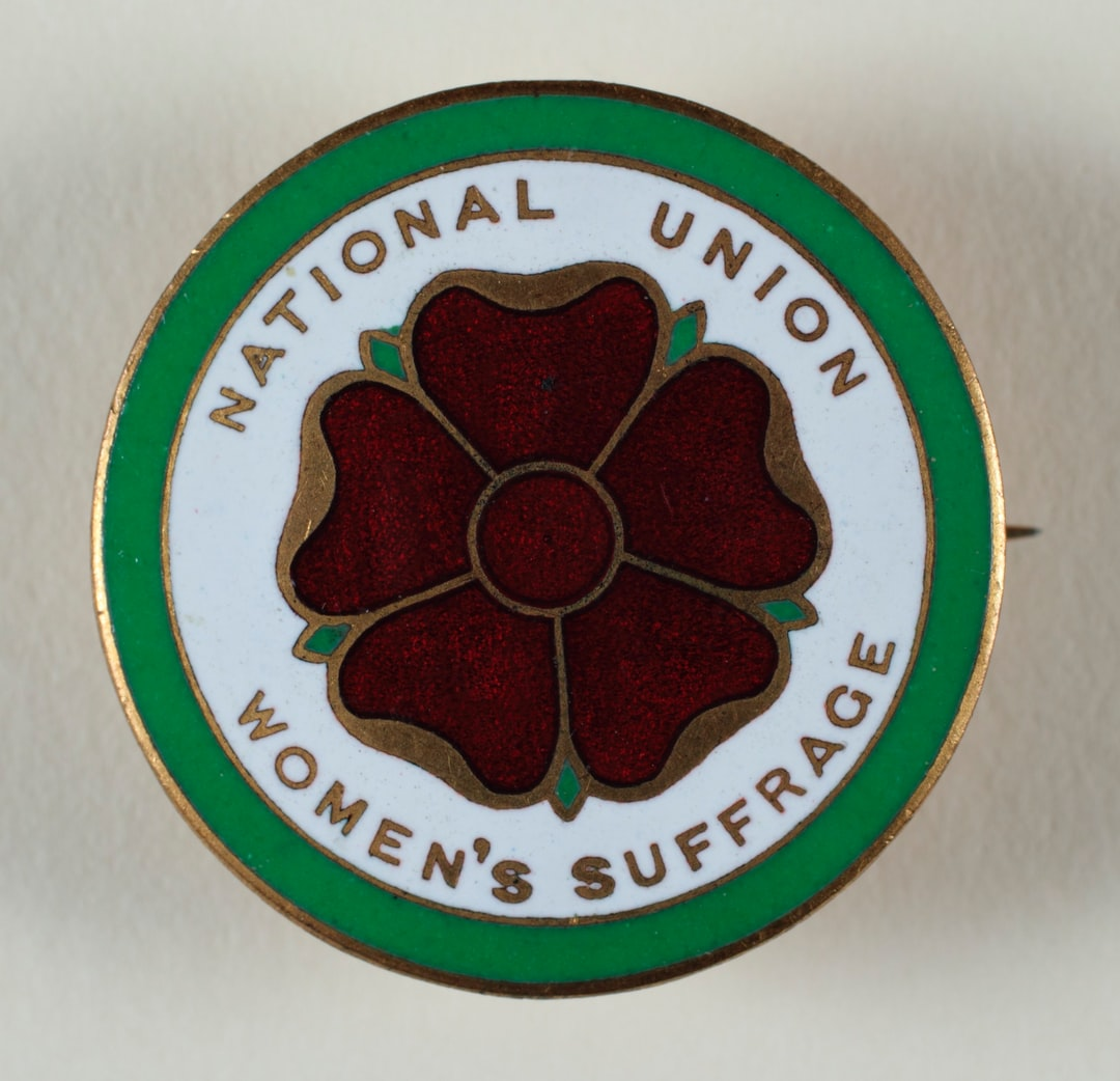 Suffrage Campaigning: National Union of Women's Suffrage Societies 1908-1918. Badge, metal, enamel, round, produced by the National Union of Women's Suffrage Societies, red, green and gold rose design with gold inscription: 'National Union of Women's Suffrage Societies' around the edge, on a white ground, green and gold border. TWL.2004.583.2