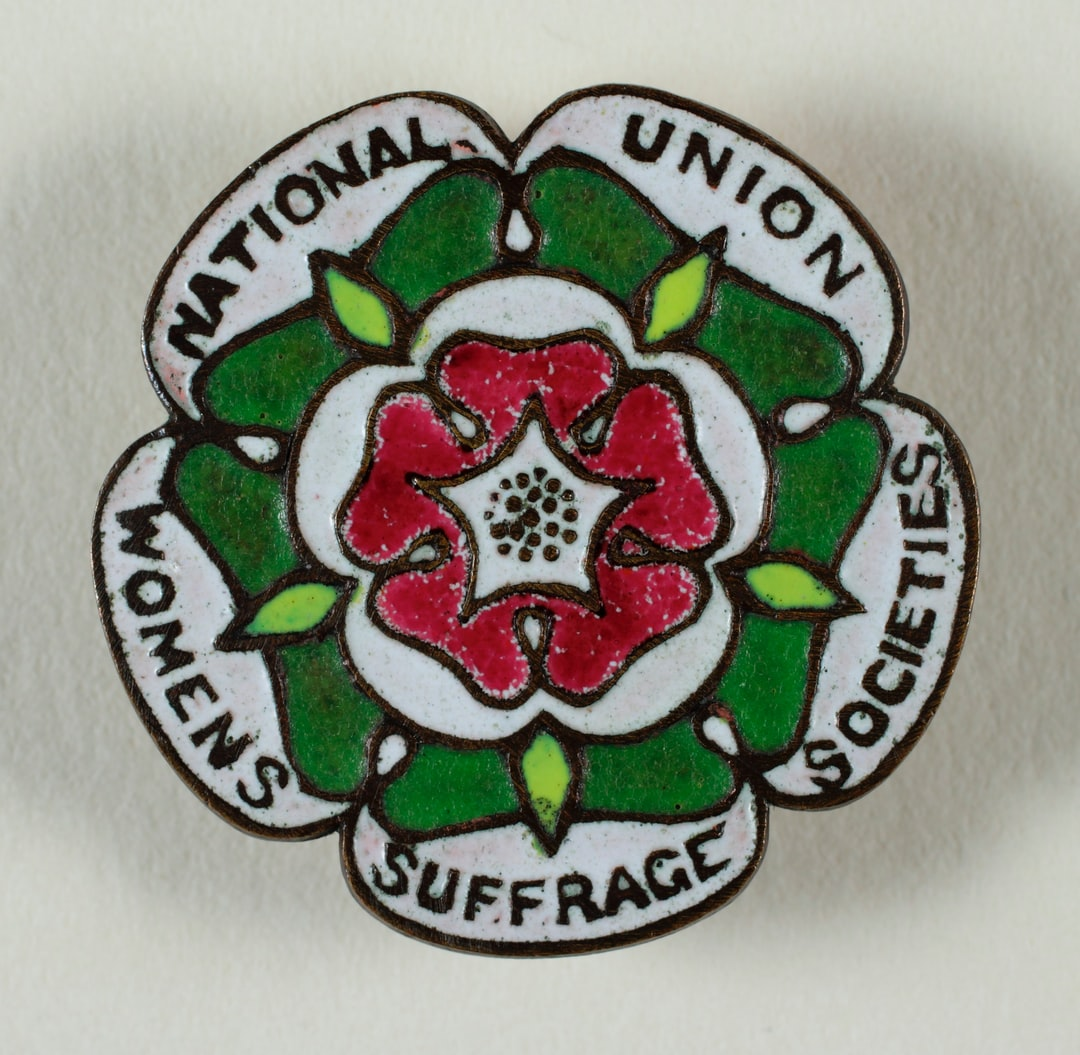 Suffrage Campaigning: National Union of Women's Suffrage Societies [NUWSS] 1908-1918. Badge, metal, enamel, rose shaped, scalloped edge, produced by the National Union of Women's Suffrage Societies, red, green, black and white rose design with black inscription: 'National Union of Women's Suffrage Societies' around the edge, black border. TWL.2004.584.1