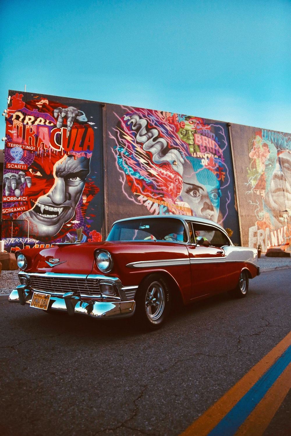 red classic car parked beside wall with graffiti