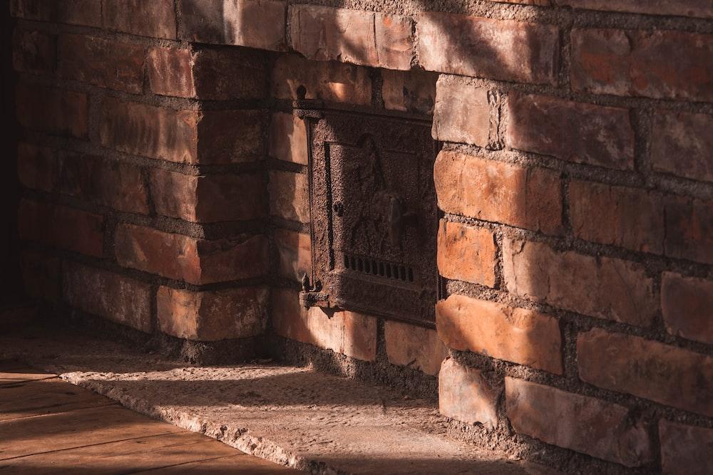 brown brick wall with black metal door