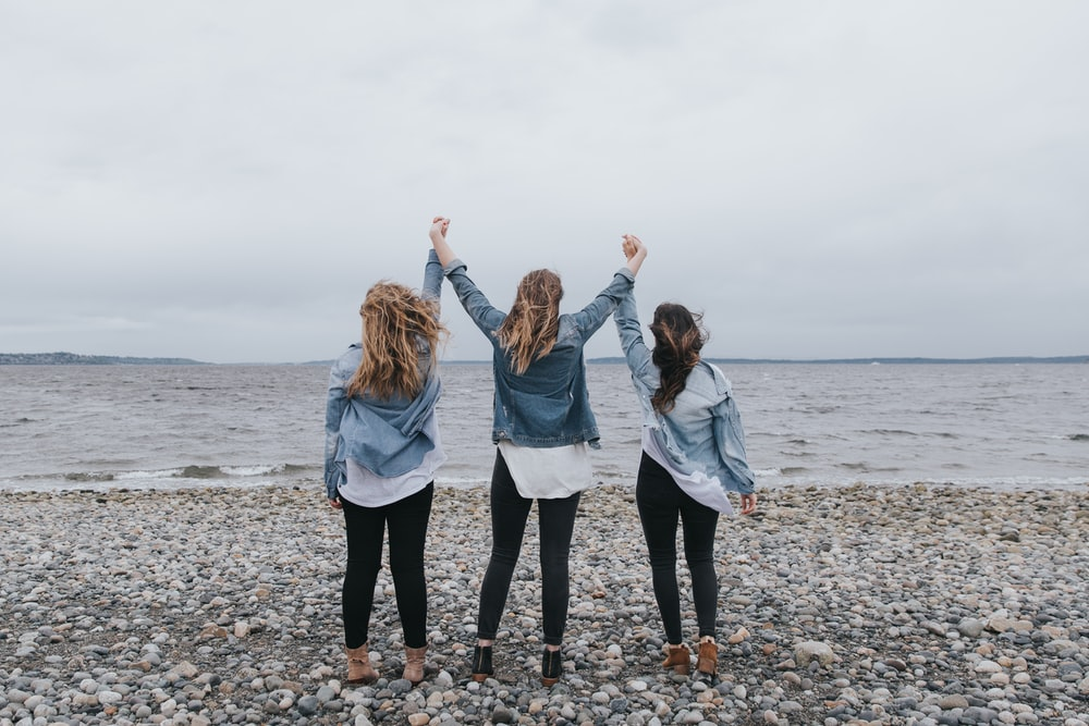 4 women standing on beach during daytime