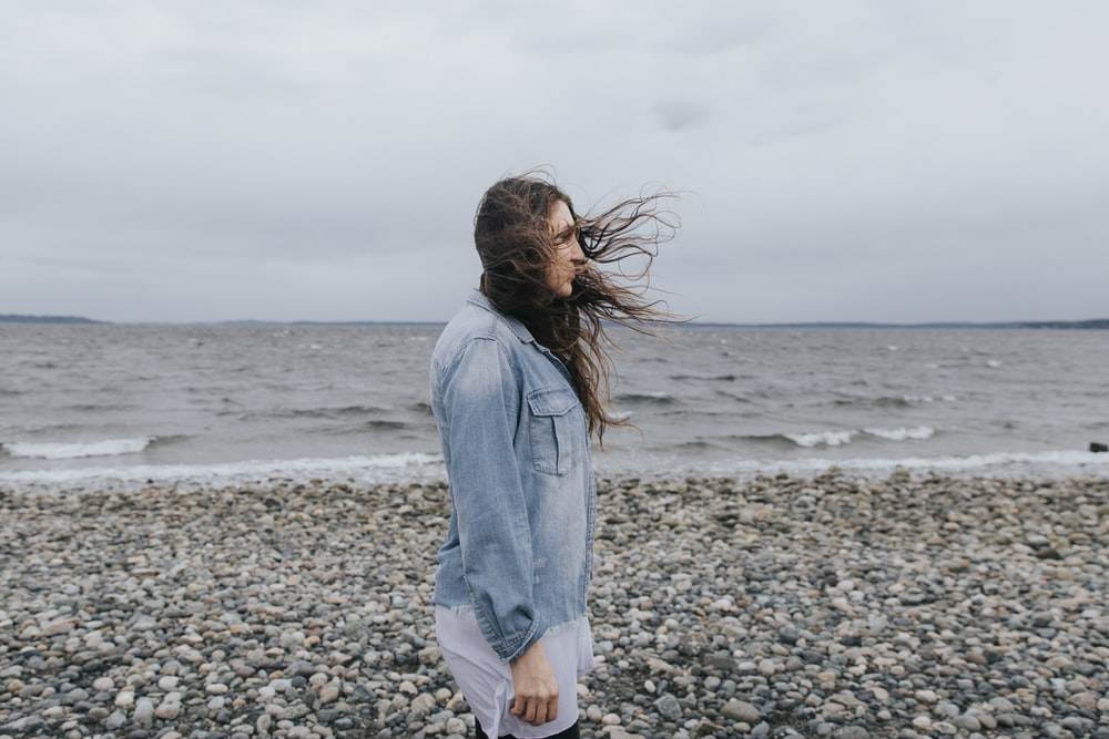 woman in blue denim jacket standing on beach shore during daytime