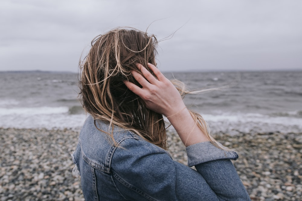 woman in blue denim jacket covering her face with her hands