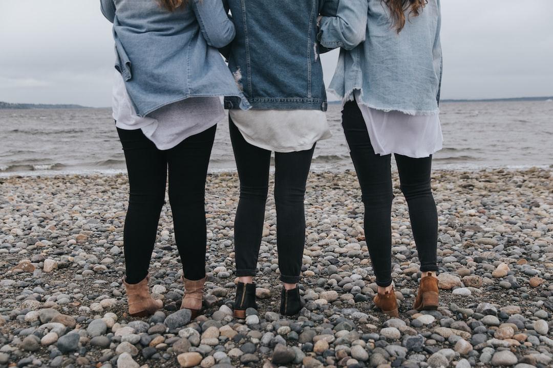 Three women linked arms on beach