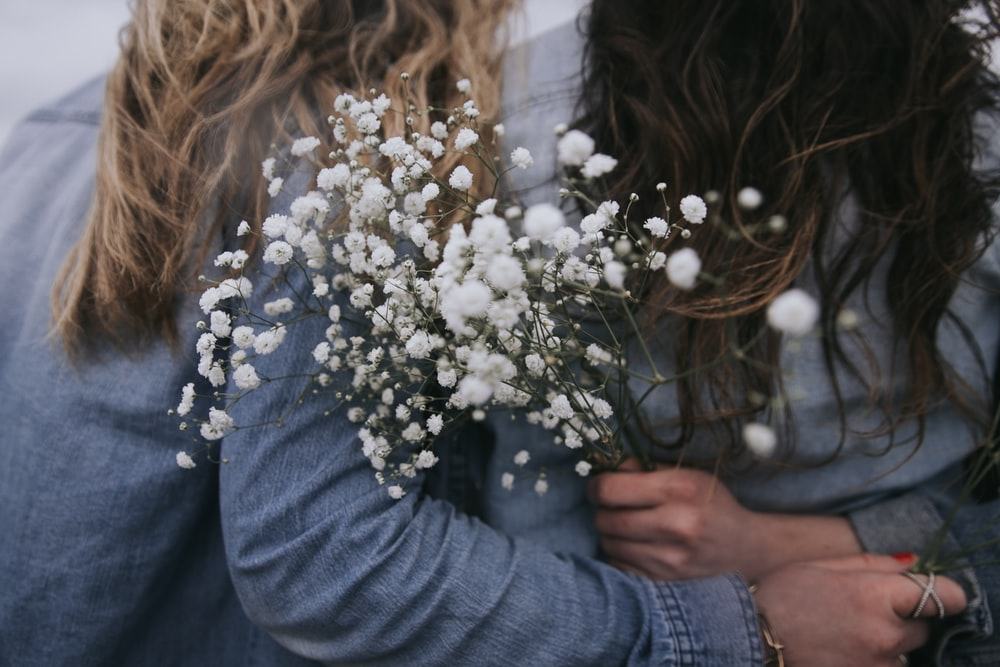 woman in gray long sleeve shirt holding white flowers