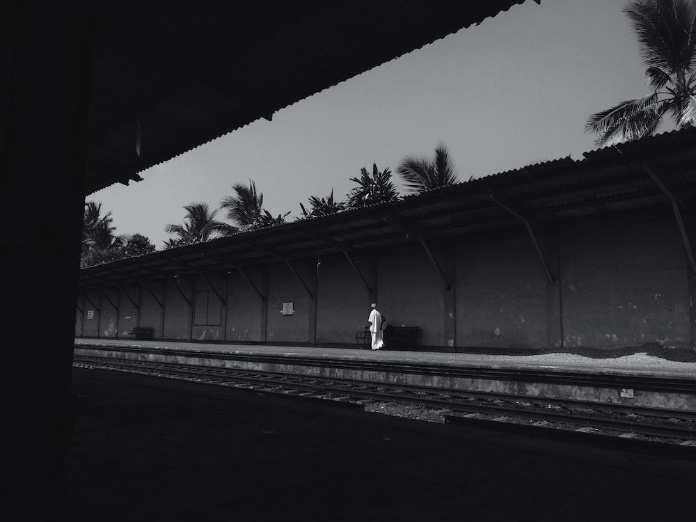 grayscale photo of man walking on train rail