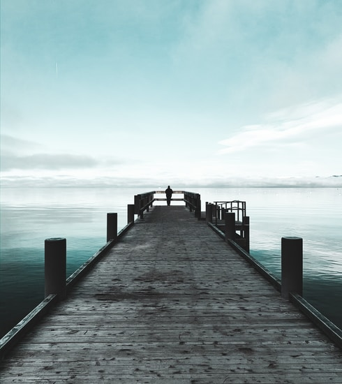 brown wooden dock on sea under white clouds during daytime