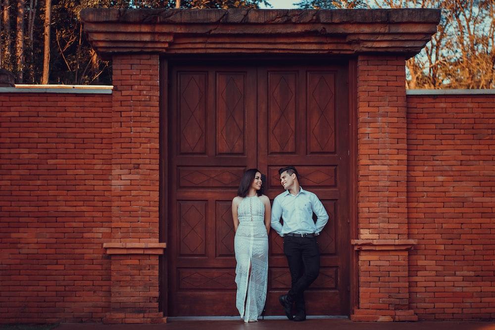 couple standing beside brown wooden door