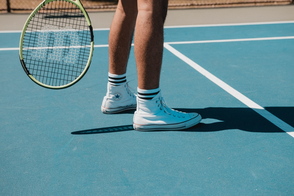 person in white nike sneakers standing on tennis court