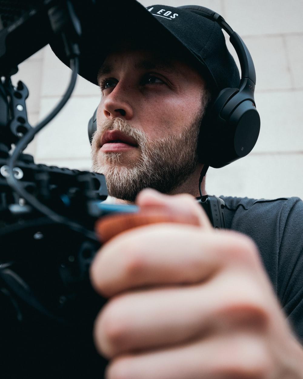 man in grey shirt wearing black headphones