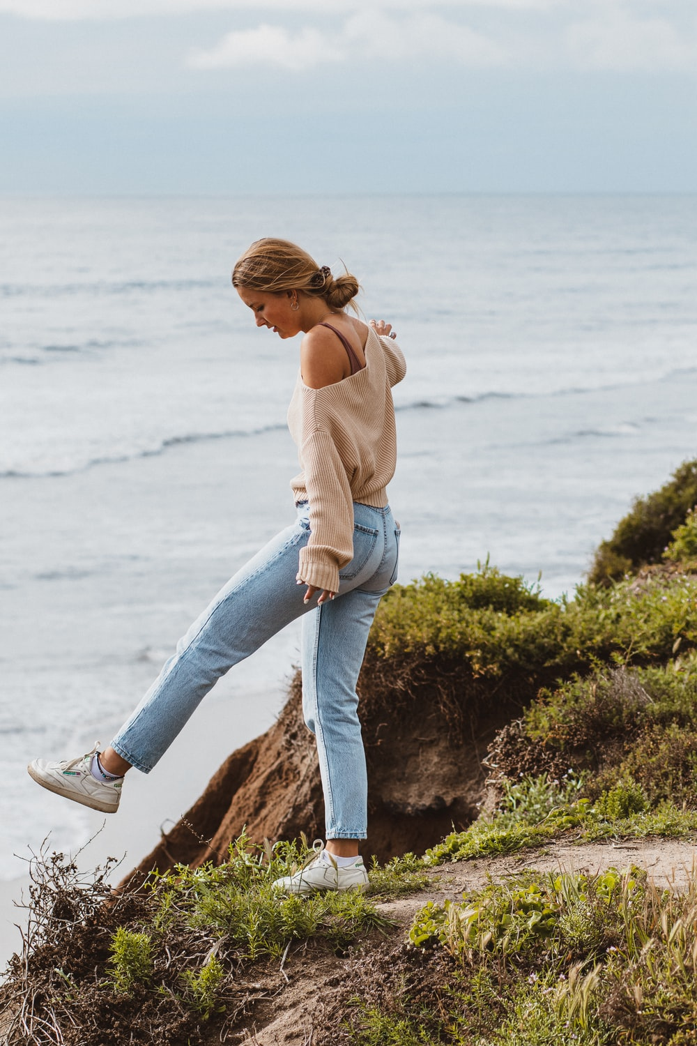 woman in brown long sleeve shirt and blue denim jeans sitting on rock near sea during