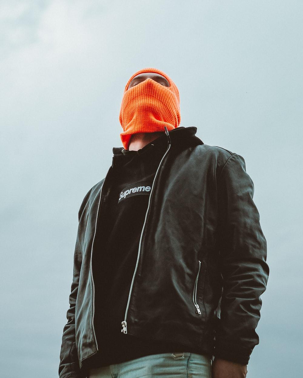 man in black jacket and orange knit cap