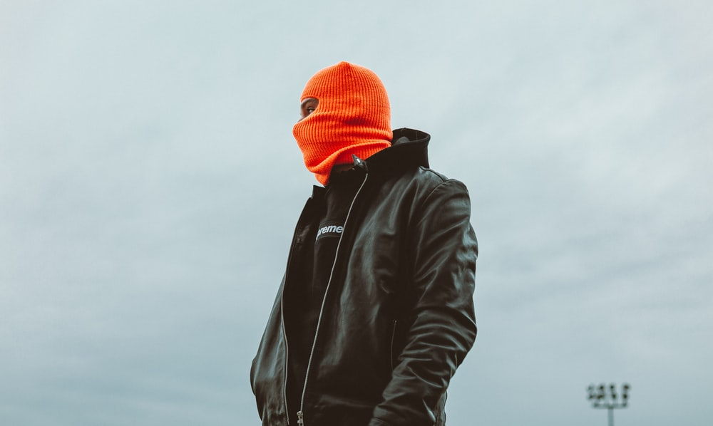man in black leather jacket and orange knit cap
