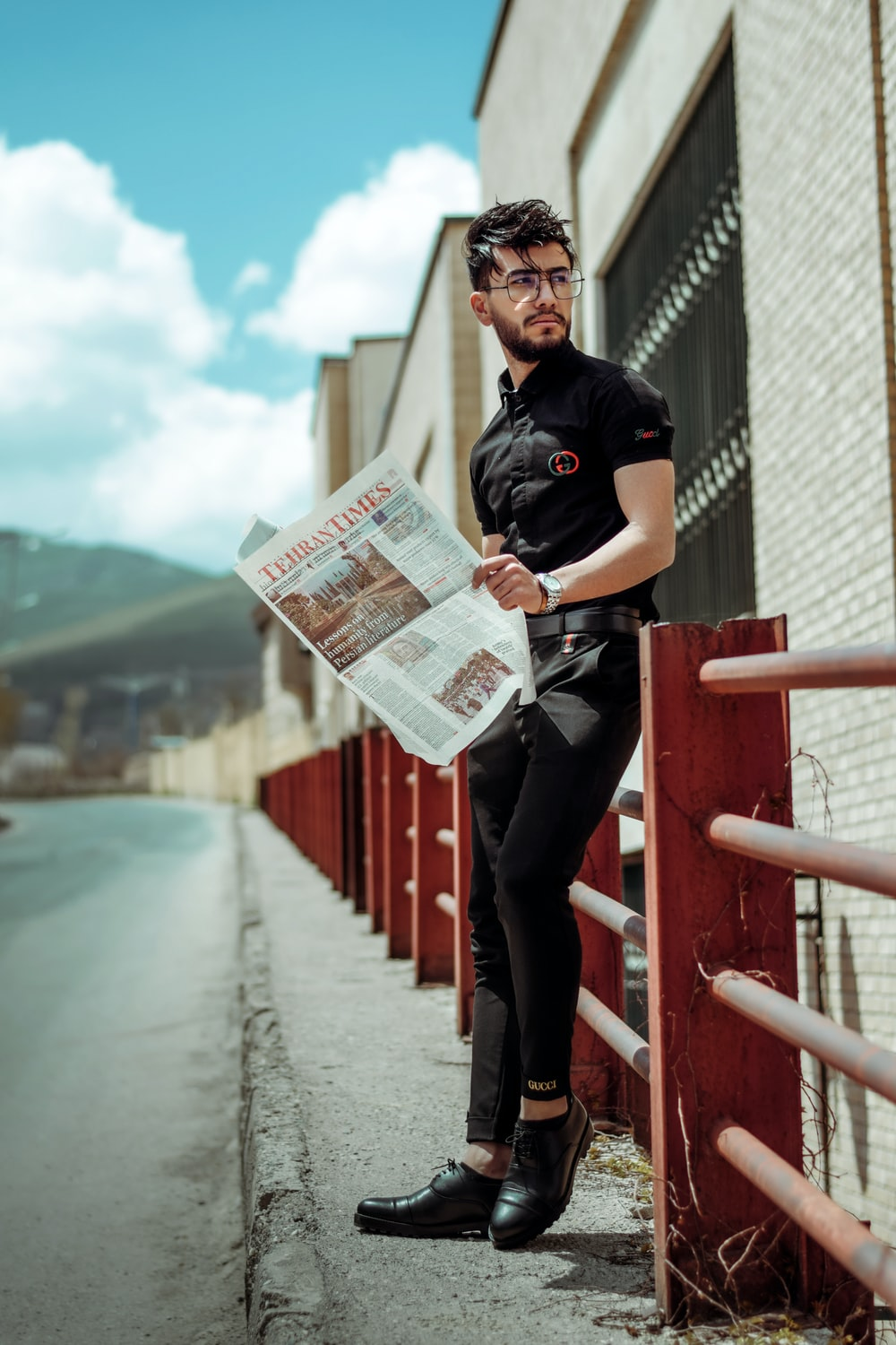 man in black polo shirt holding newspaper