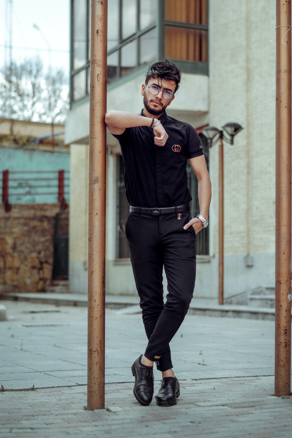 man in black polo shirt and black pants wearing black sunglasses standing on sidewalk during daytime