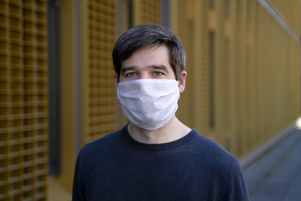 man in black crew neck shirt with white face mask