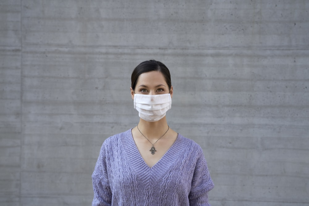 woman in blue v neck sweater wearing white face mask