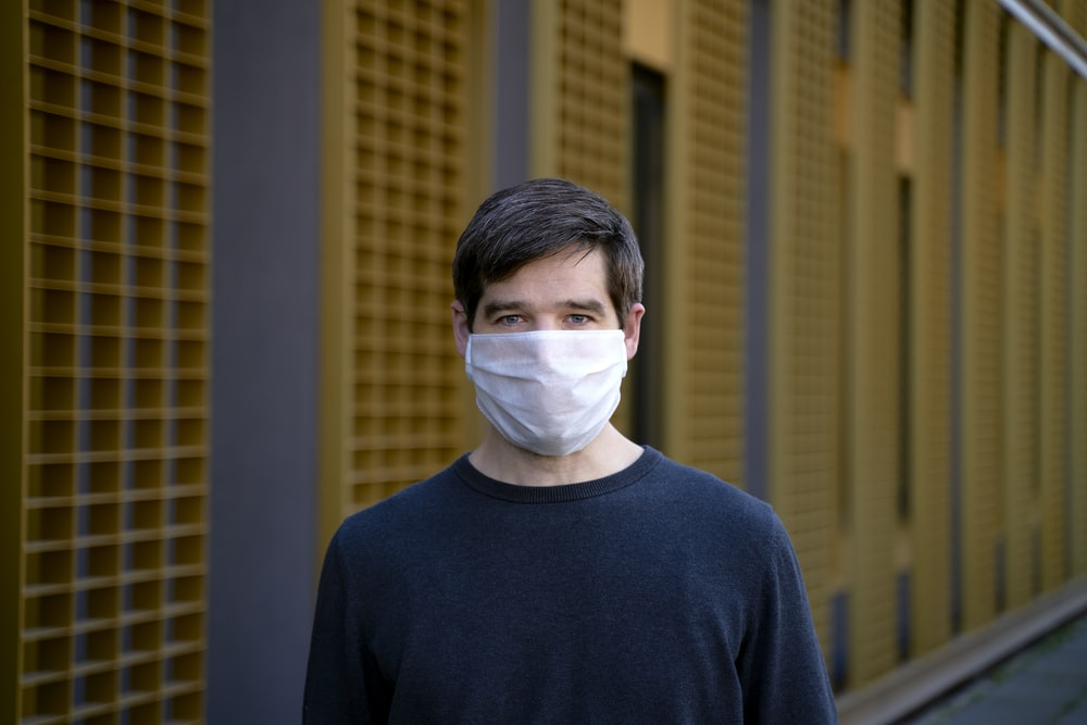 man in black crew neck shirt with white mask