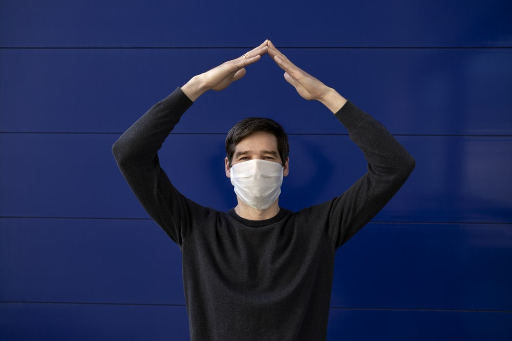 man in black long sleeve shirt wearing white face mask