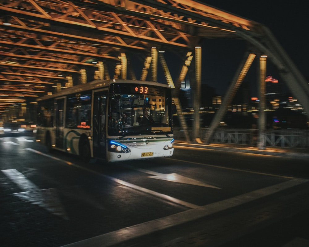 white bus on the road during night time