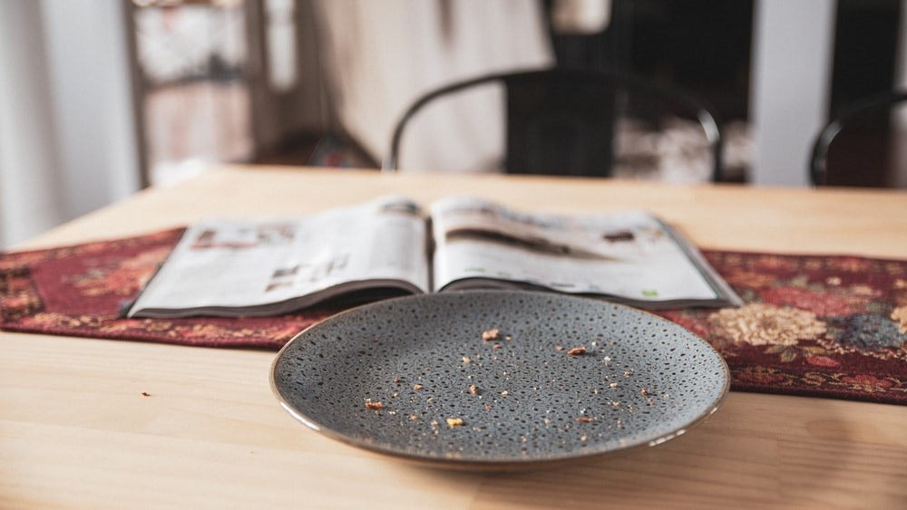 black round plate on brown wooden table