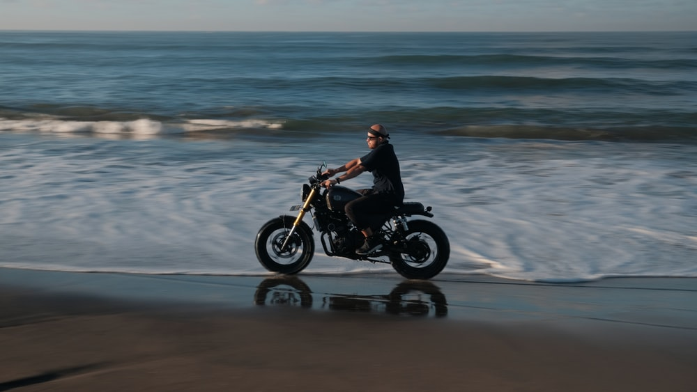 man in black jacket riding motorcycle on beach during daytime