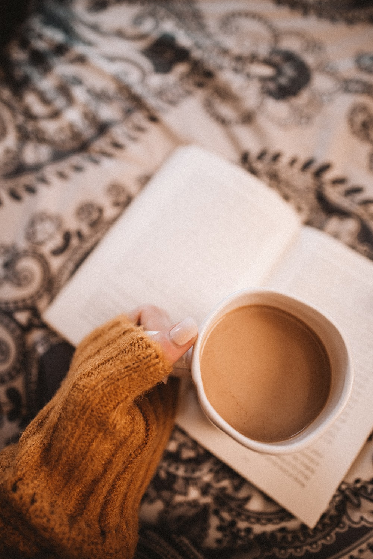 person holding white ceramic mug with brown liquid