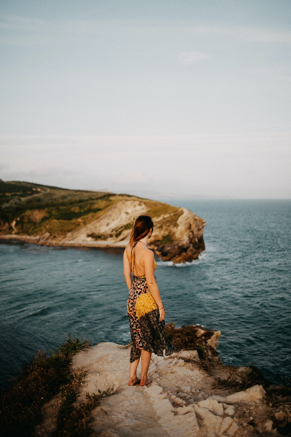 woman in black and brown floral dress standing on rock formation near body of water during