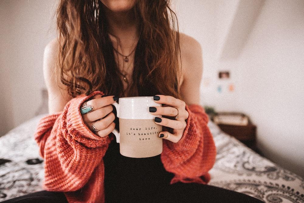 woman in black tank top holding white ceramic mug
