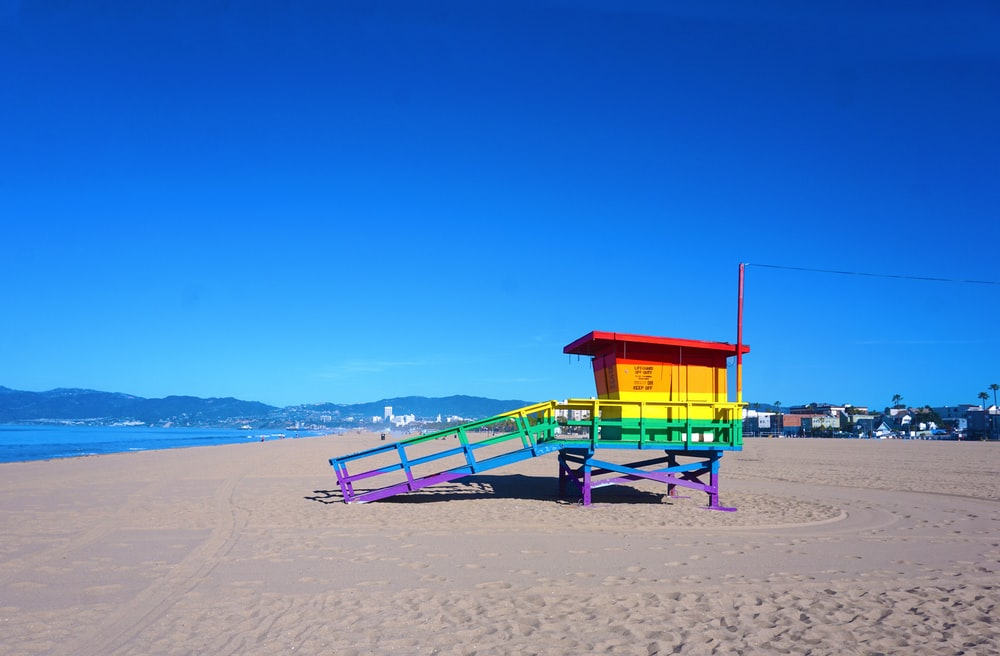 red and blue wooden lifeguard house on beach shore during daytime