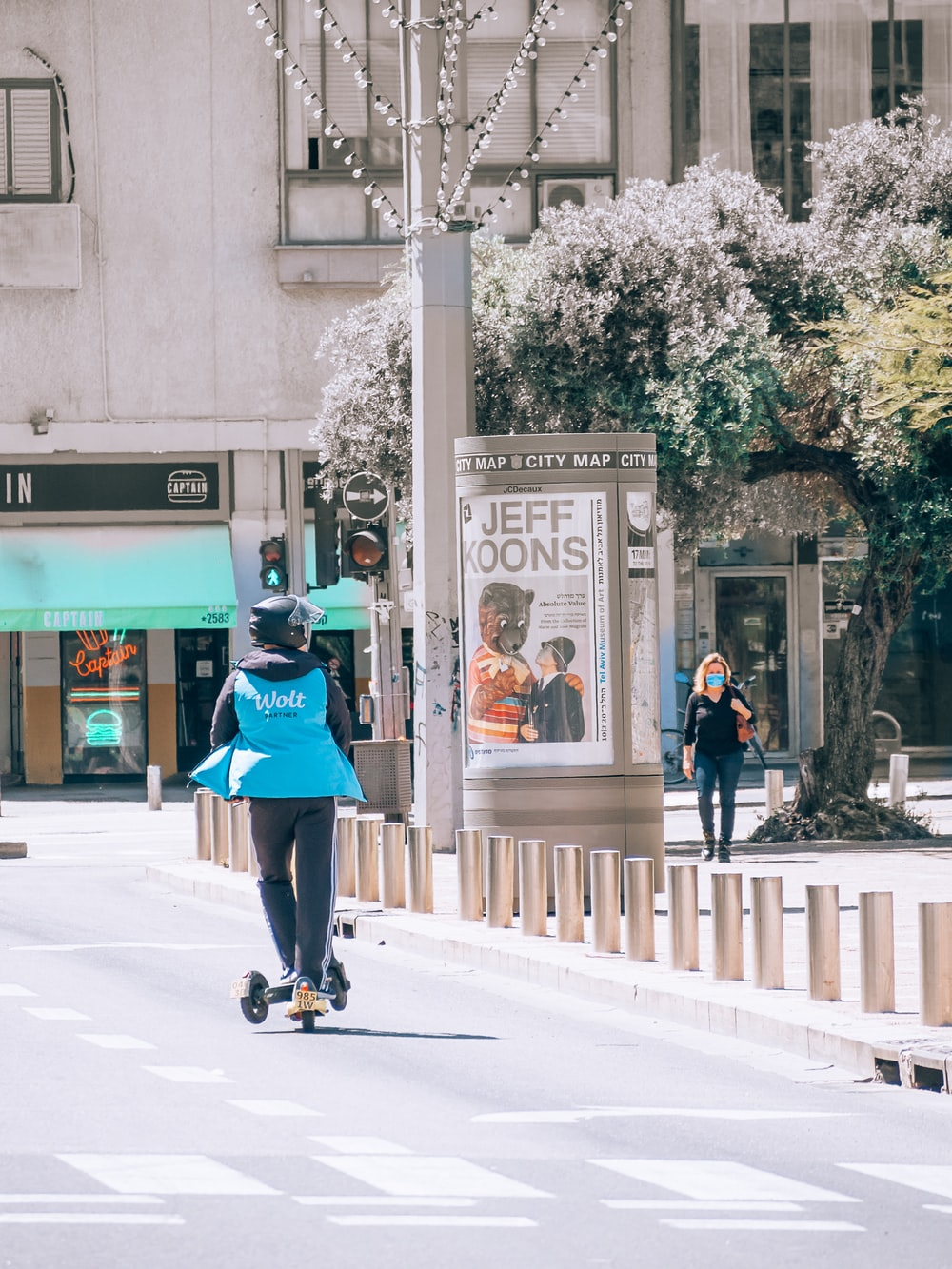 woman in green jacket and black pants riding on black skateboard during daytime