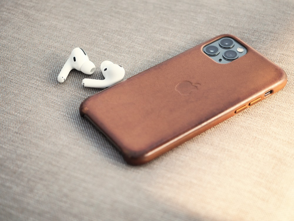 brown leather smartphone case beside white earbuds