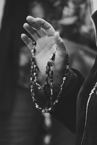 grayscale photo of person wearing beaded bracelet